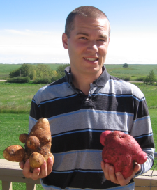 Dave holding a Russet & a Viking potato